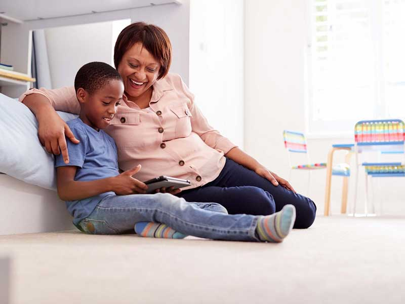 Grandmother sitting with grandson using an ipad