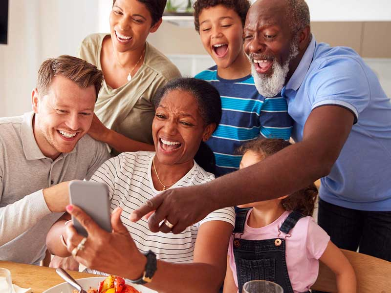 Family sitting around the table laughing at a video on a phone