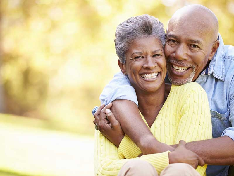 Older couple cuddling and smiling for the camera