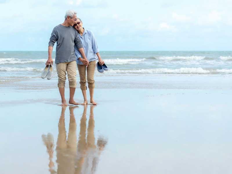 Older couple walking barefoot on the beach